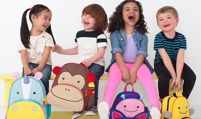 four children carrying Skip Hop bookbags